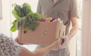 A box of produce being handed from one person to another